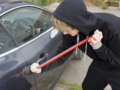 A White Burglar prying car window open with crowbar on AOL