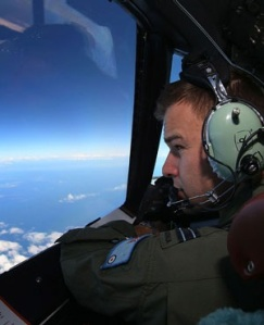 RAAF Flight Lieutenant Russell Adams looks out from the cockpit of a AP-3C Orion during a search mission for missing Malaysia Airline flight MH370 in the Southern Indian Ocean. (Paul Kane, AFP)